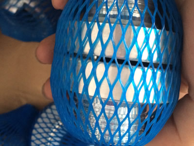 Two aluminum storz male threads buckle together in blue plastic mesh.